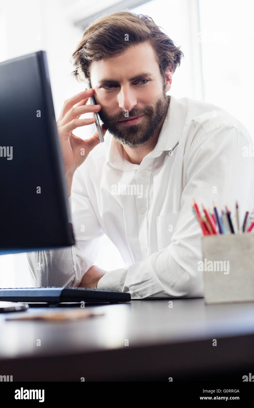 A man passing a call in front of this desk  at the office - Stock Image