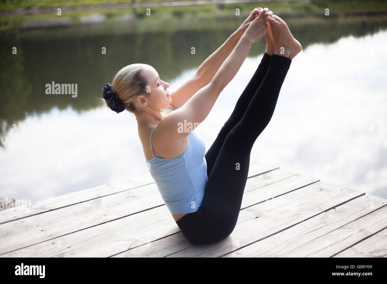 Serene fit young beautiful woman practicing yoga outdoors in park on the lake on summer day, sitting in Ubhaya Padangusthasana - Stock Image