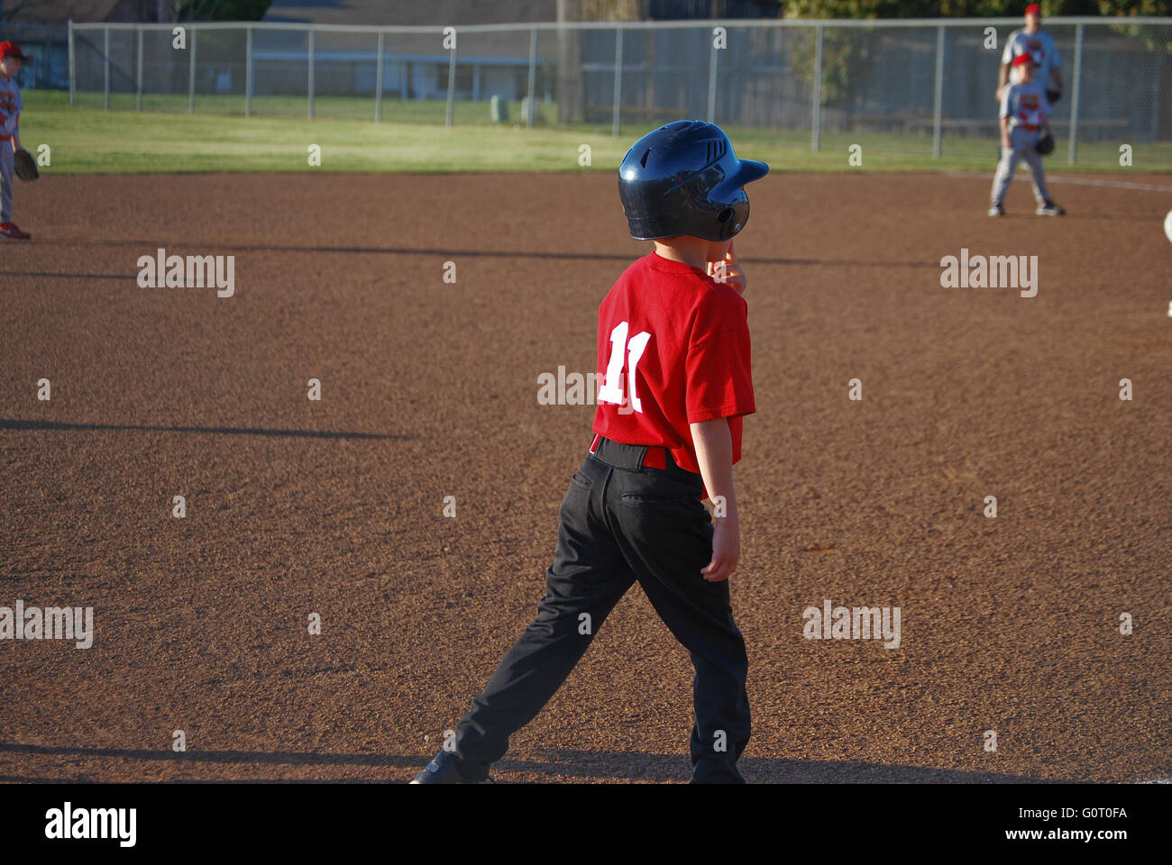 Youth baseball player standing on third base waiting to run the bases. - Stock Image