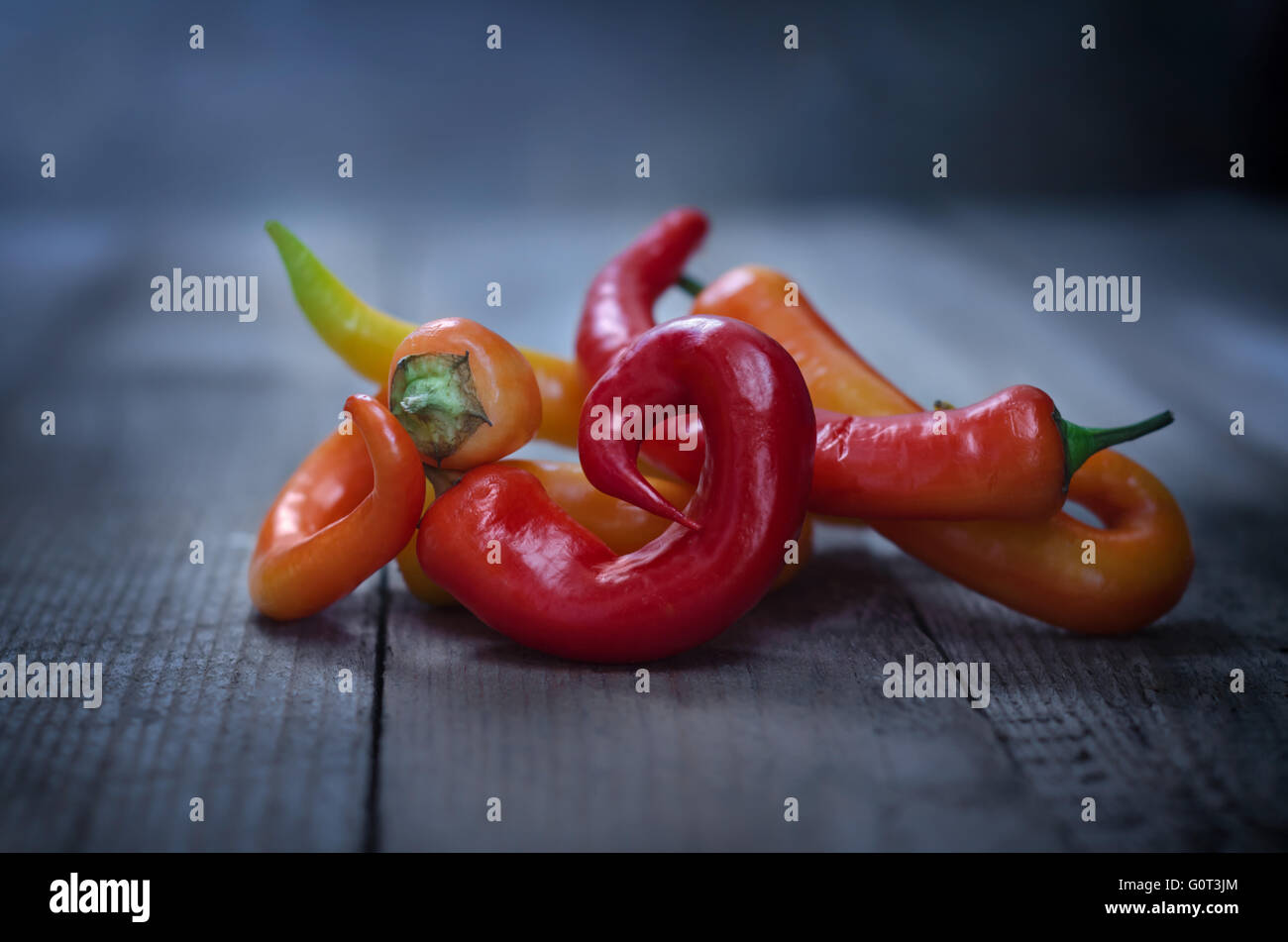 Colorful chili peppers on old wooden background. - Stock Image