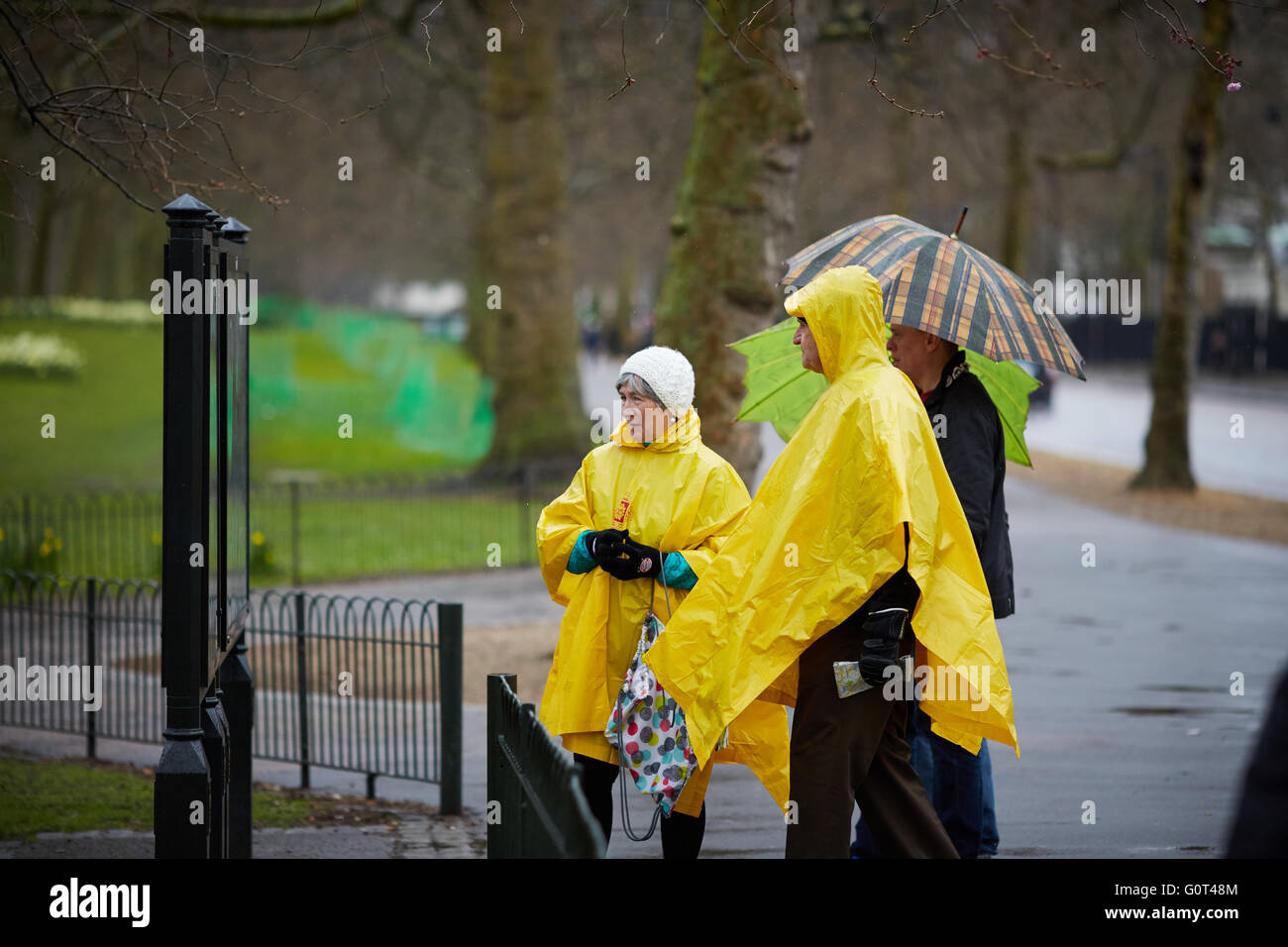 Tourists eating yellow disposable rain coats sheets ponchos rain wet weather plastic rain coat cover stay dry Stock Photo