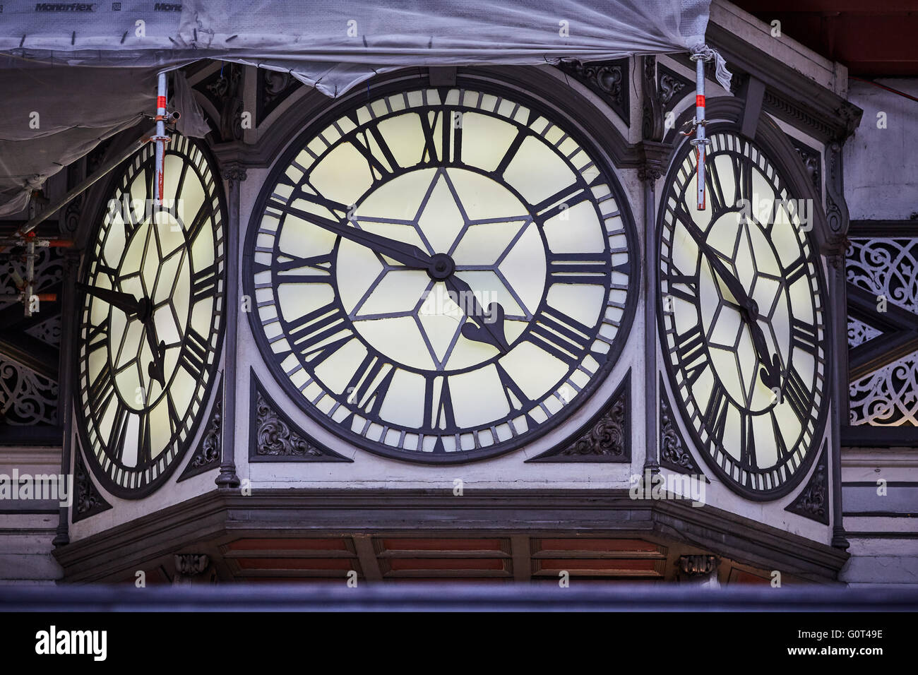 London paddington railway station clock large 3 faces roman numeral scaffolding restoration clock face hands time - Stock Image