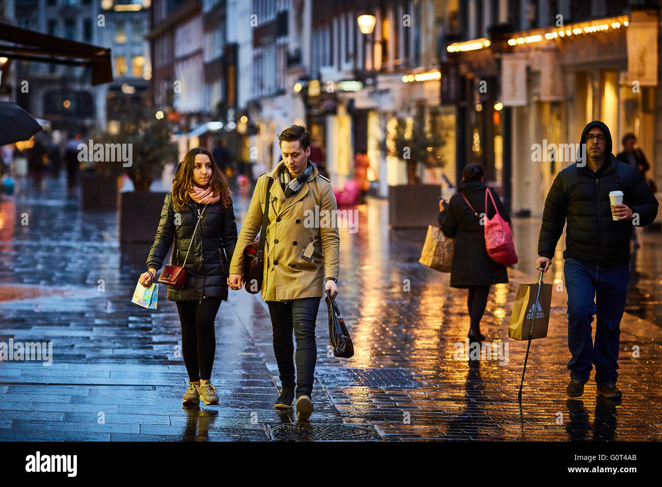 London street at  night and wet raining evening shopper walking - Stock Image