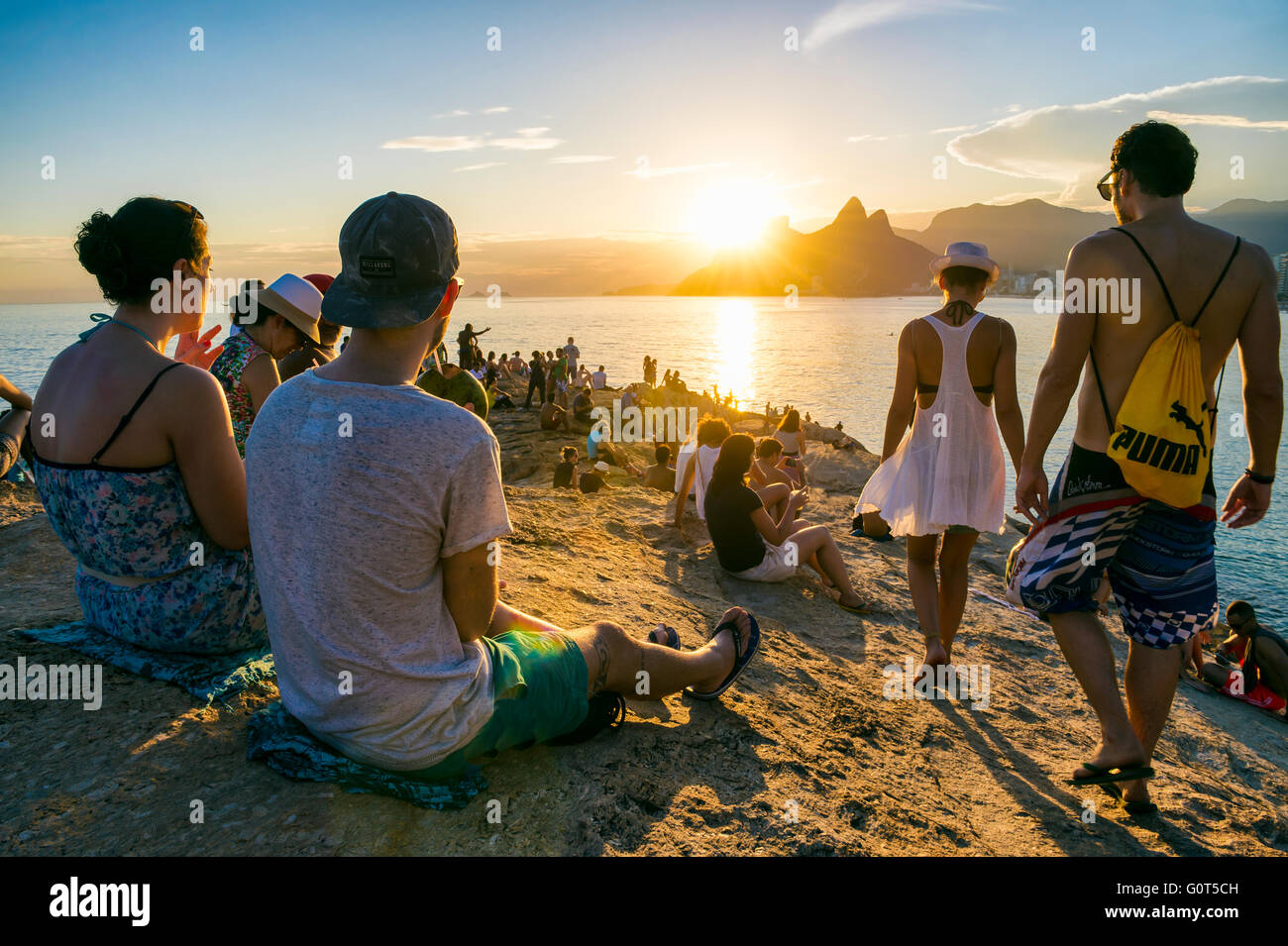 RIO DE JANEIRO - FEBRUARY 26, 2016: Crowds of people gather to watch the sunset on the rocks at Arpoador in a popular - Stock Image