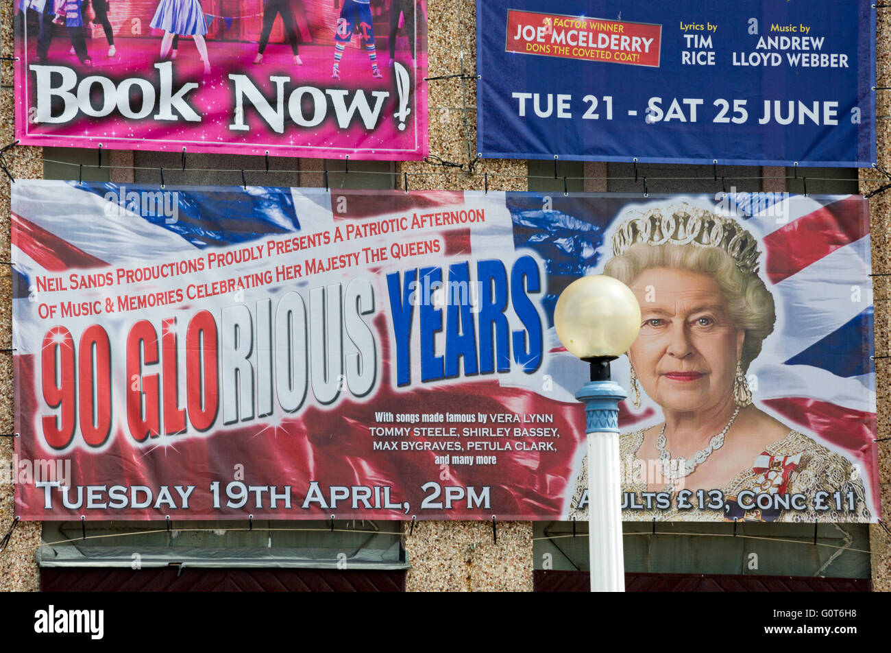 Banner promoting event to celebrate the Queen's 90 glorious years on outside wall of Weymouth Pavilion in May - Stock Image