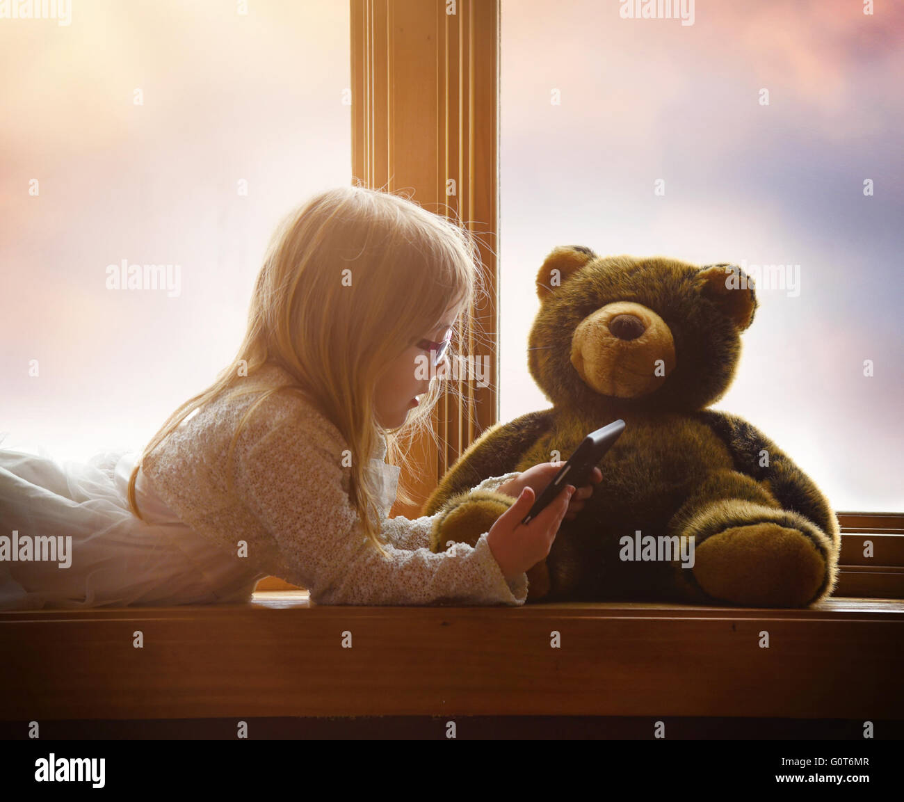 A little child is playing with an electronic tablet in a window with her teddy bear for a game, app or entertainment - Stock Image