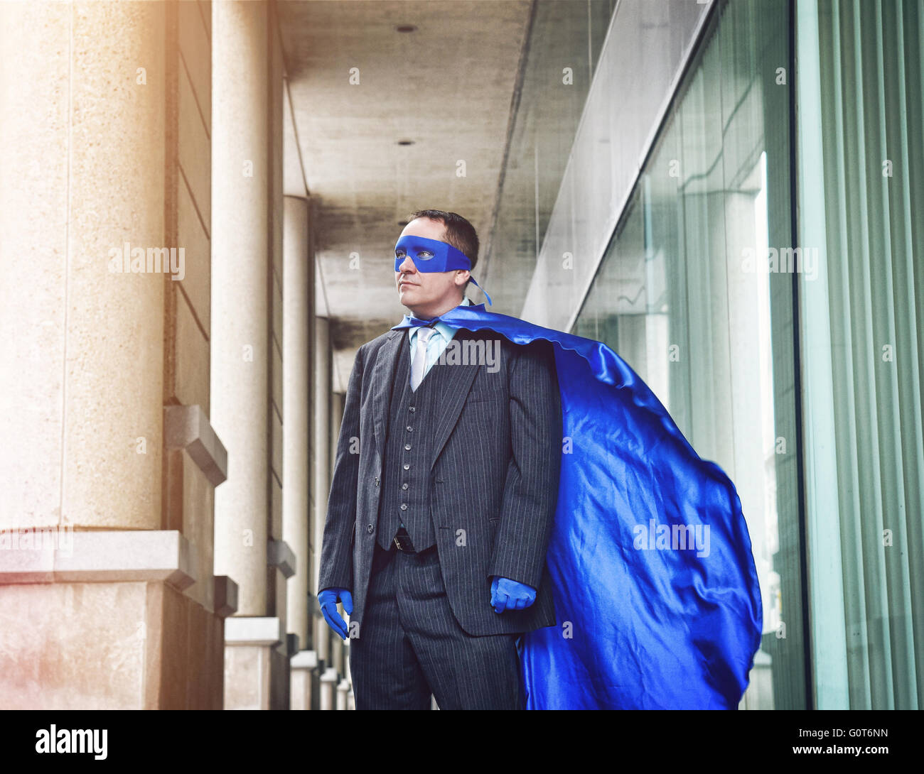 A super business man is wearing a blue cape confident in the city for a success, entrepreneur or inspiration concept. - Stock Image