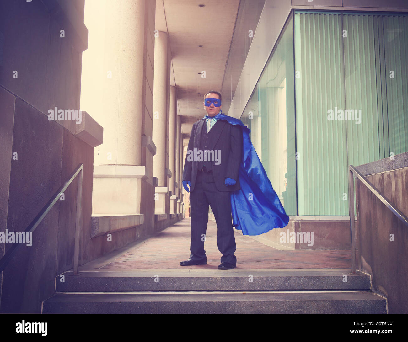 A business man is wearing a super hero blue costume with a suit in a city for a career success or innovation concept. - Stock Image