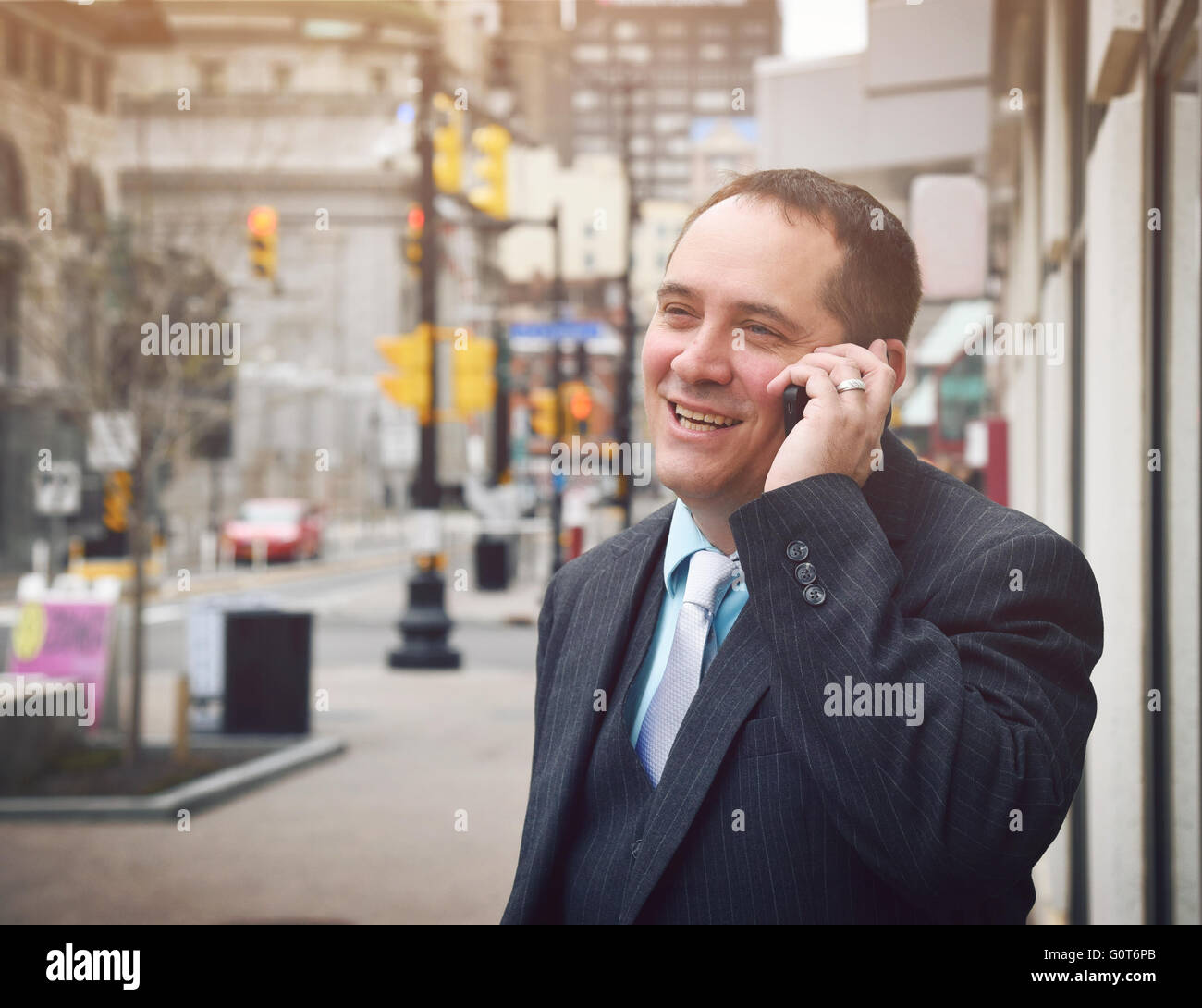 A business man is talking on a cell phone outside in a city wearing a suit and smiling for a success or communication - Stock Image
