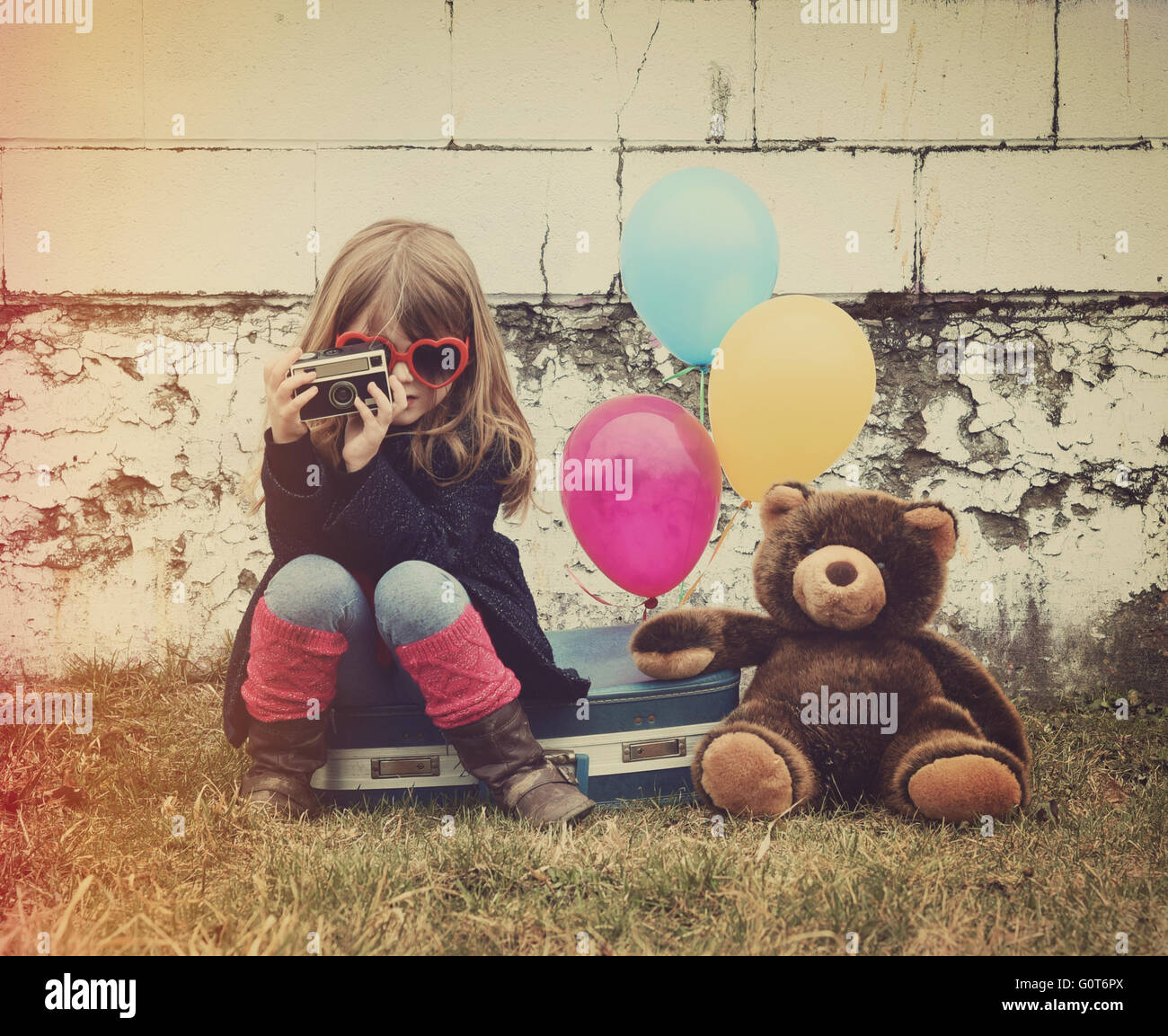 A photo of a vintage child taking a picture with old camera against a brick wall, balloons and a teddy bear for - Stock Image