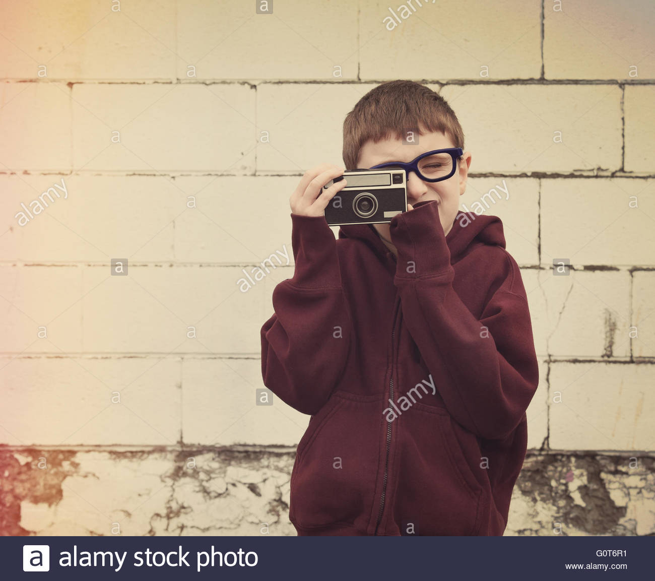 A young child is taking a photograph with an old vintage camera against a brick wall for a retro technology or image - Stock Image