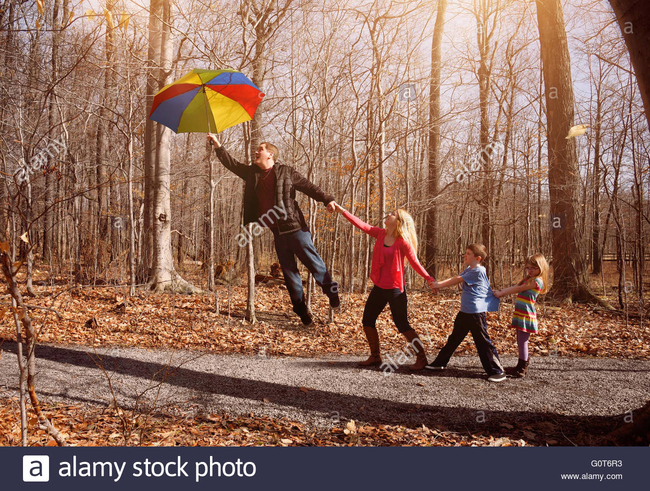 A family is holding hands together and flying up in a rainbow umbrella outside for a imagination, support or happiness - Stock Image