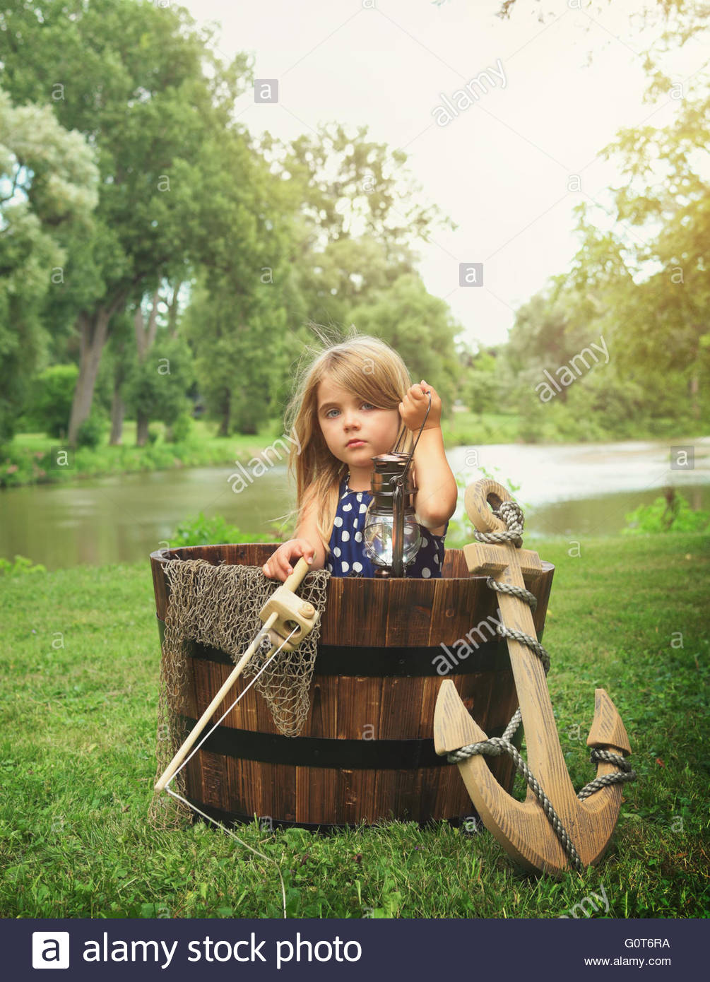 A little child is sitting in a wooden boat with an anchor pretending to fish for an imagination or exploration concept. - Stock Image