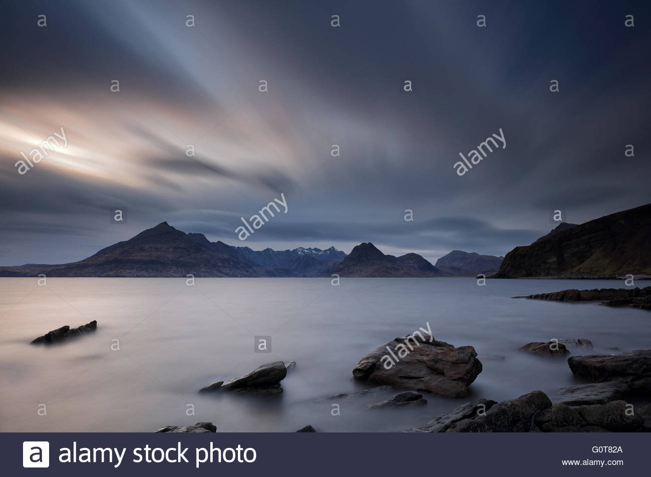 A long exposure of the rocky shore at Elgol on the Isle of Skye, with the snow-capped Cuillin mountains in the distance. - Stock Image