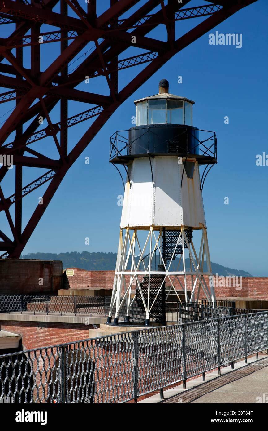 Golden Gate Bridge span arcing over lighthouse, Fort Point National Historic Site, San Francisco, California USA - Stock Image