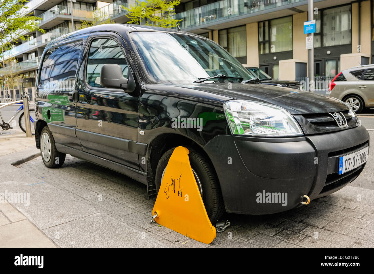 Yellow parking clamp attached to a Peugeot car/van in Dublin after it was parked illegally. - Stock Image
