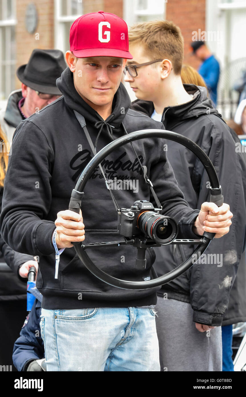 Man uses a wheel brace rig to steady an SLR camera while shooting video. - Stock Image