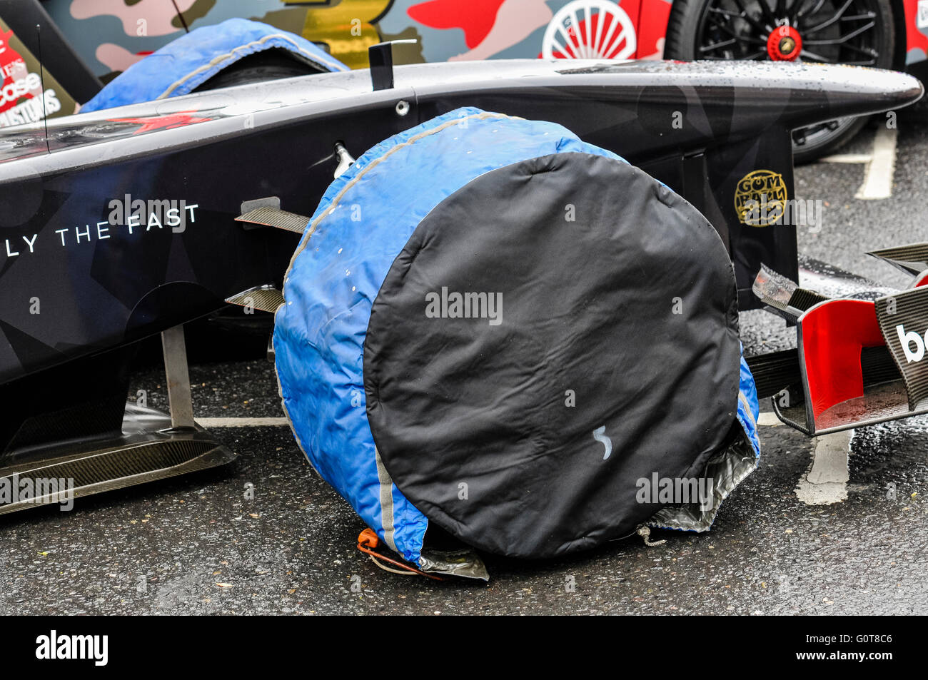 Tyre warmer jackets on the front wheels of a Formula 1 racing car. - Stock Image