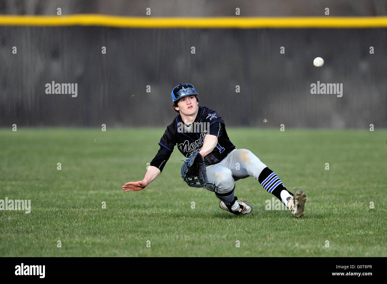 Center fielder making a diving attempt to come up with a soft line drive during a high school baseball game. USA. - Stock Image