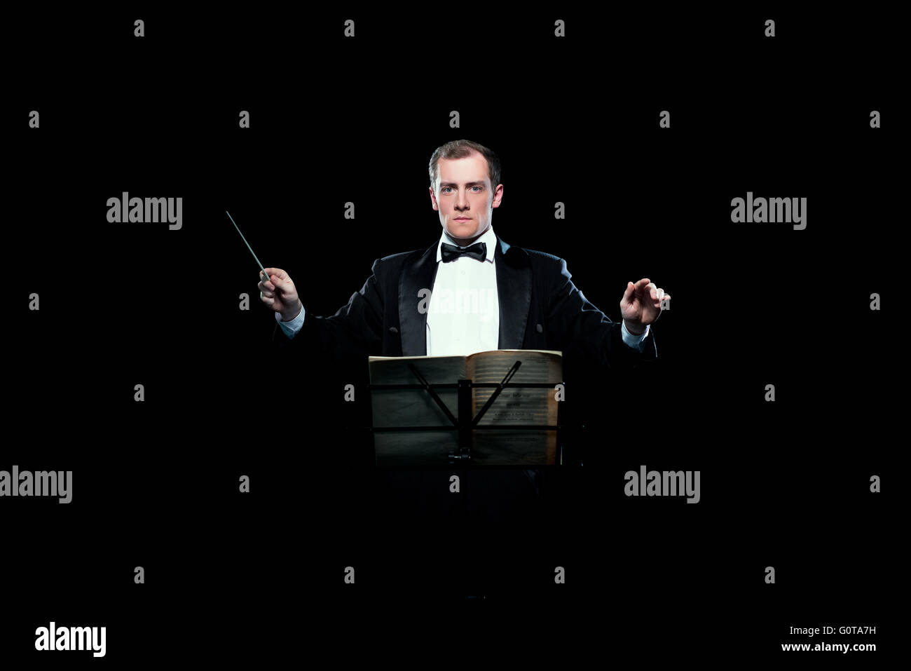 Studio photo of music conductor holding his baton - Stock Image