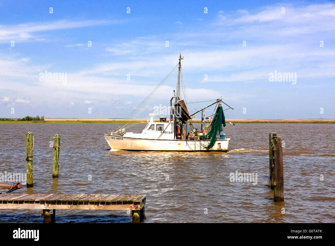 Fishing boat sails out of the estuary at Apalachicola, Florida into the Gulf of Mexico - Stock Image