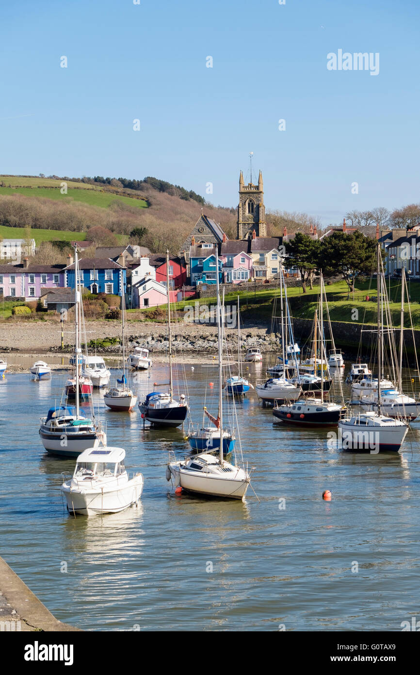 Looking along Afon Aeron River estuary to church with boats moored in harbour at high tide in coastal town. Aberaeron - Stock Image