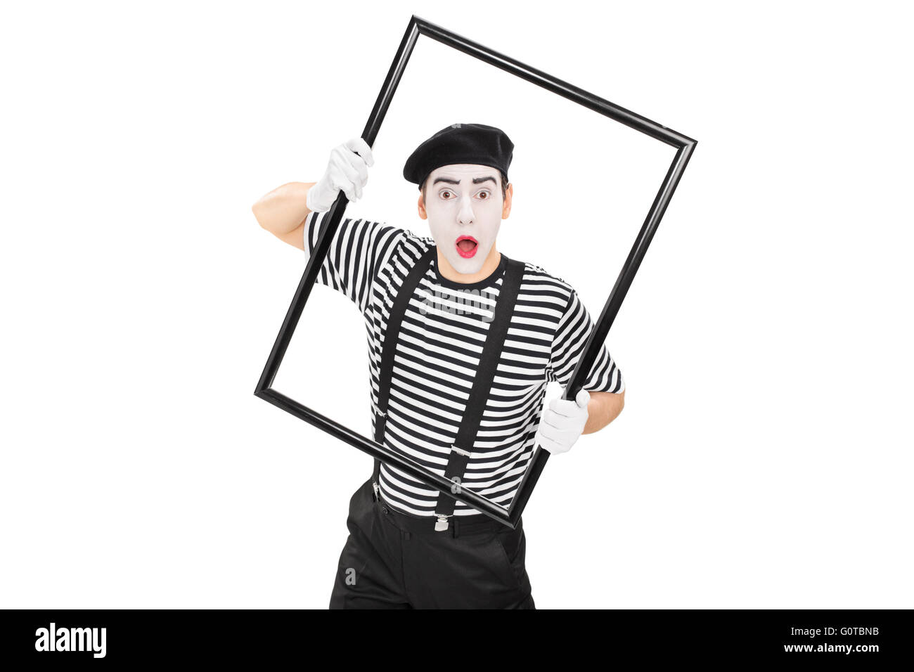 Young mime artist performing with a large black picture frame isolated on white background - Stock Image