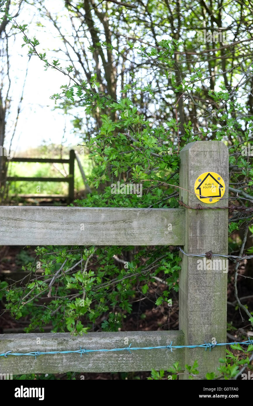 Stile on a British Public Footpath complete with yellow sign and barbed wire, May 2016 - Stock Image