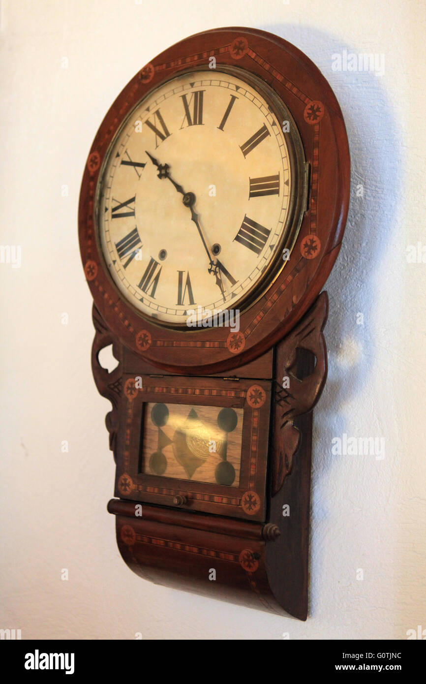 Old wooden vintage antique wind up clock with roman numerals - Stock Image