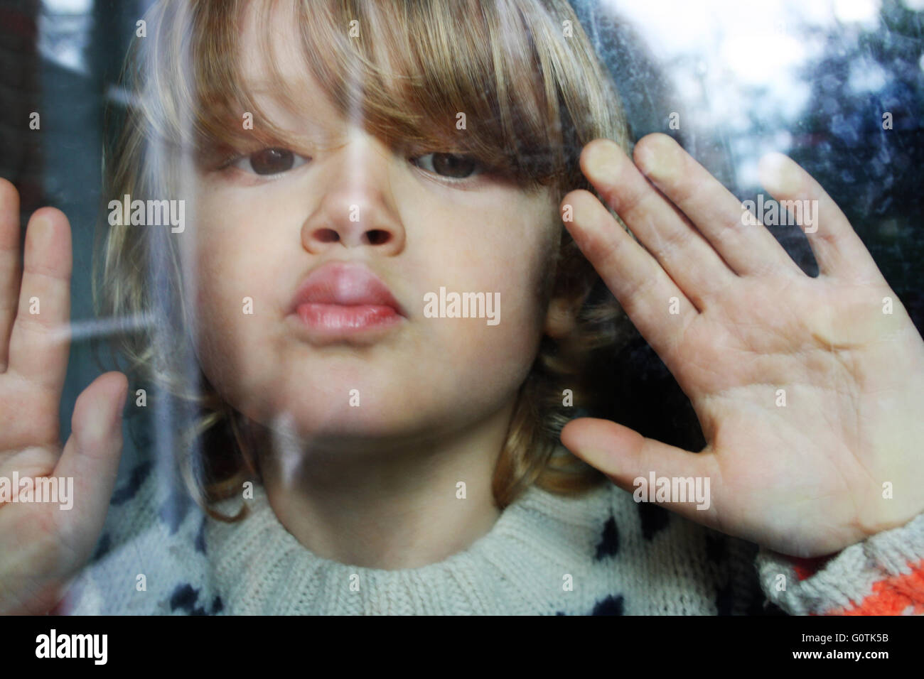 Close-up portrait of boy pressing lips and hands against window - Stock Image
