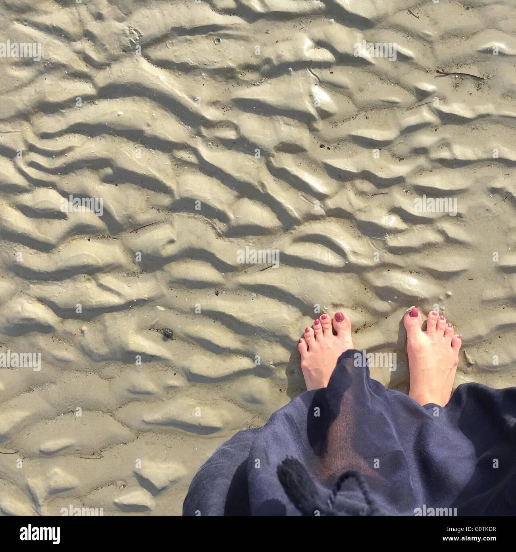 Overhead view of feet on beach Stock Photo
