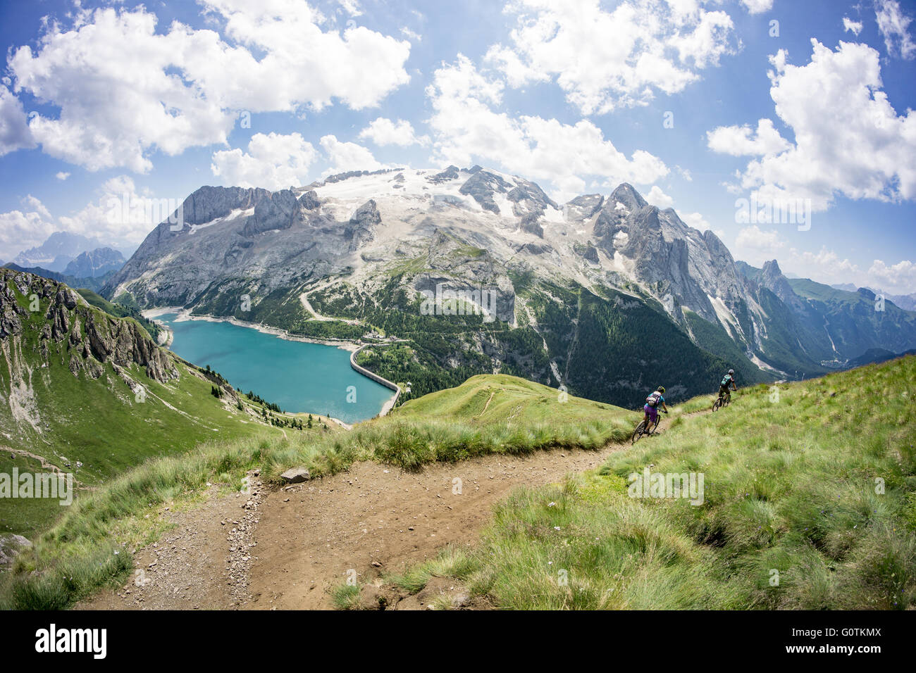 Man and woman riding mountain bikes along trail, Dolomites, Italy Stock Photo
