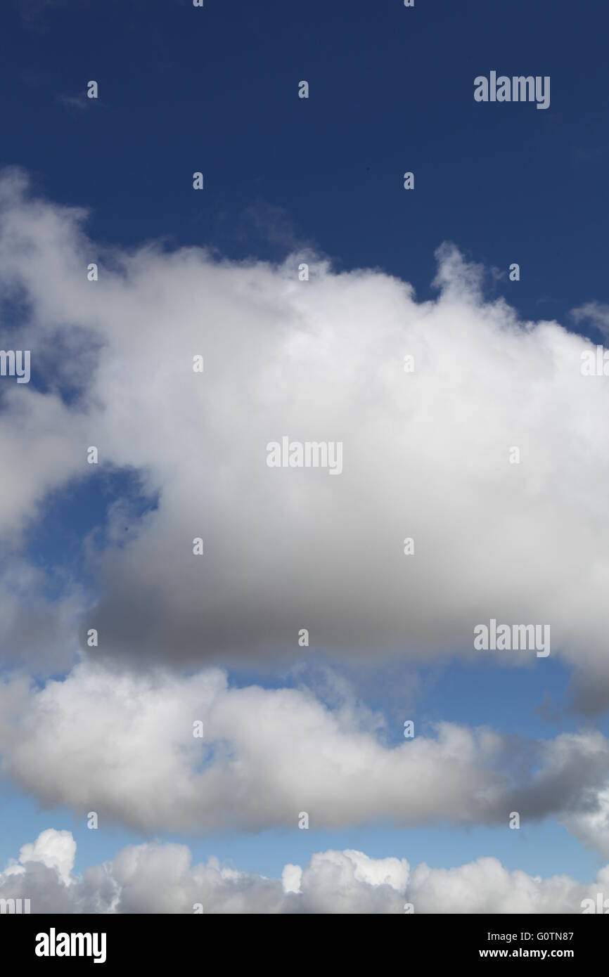 White fluffy clouds against a deep blue background during the Summer - Stock Image