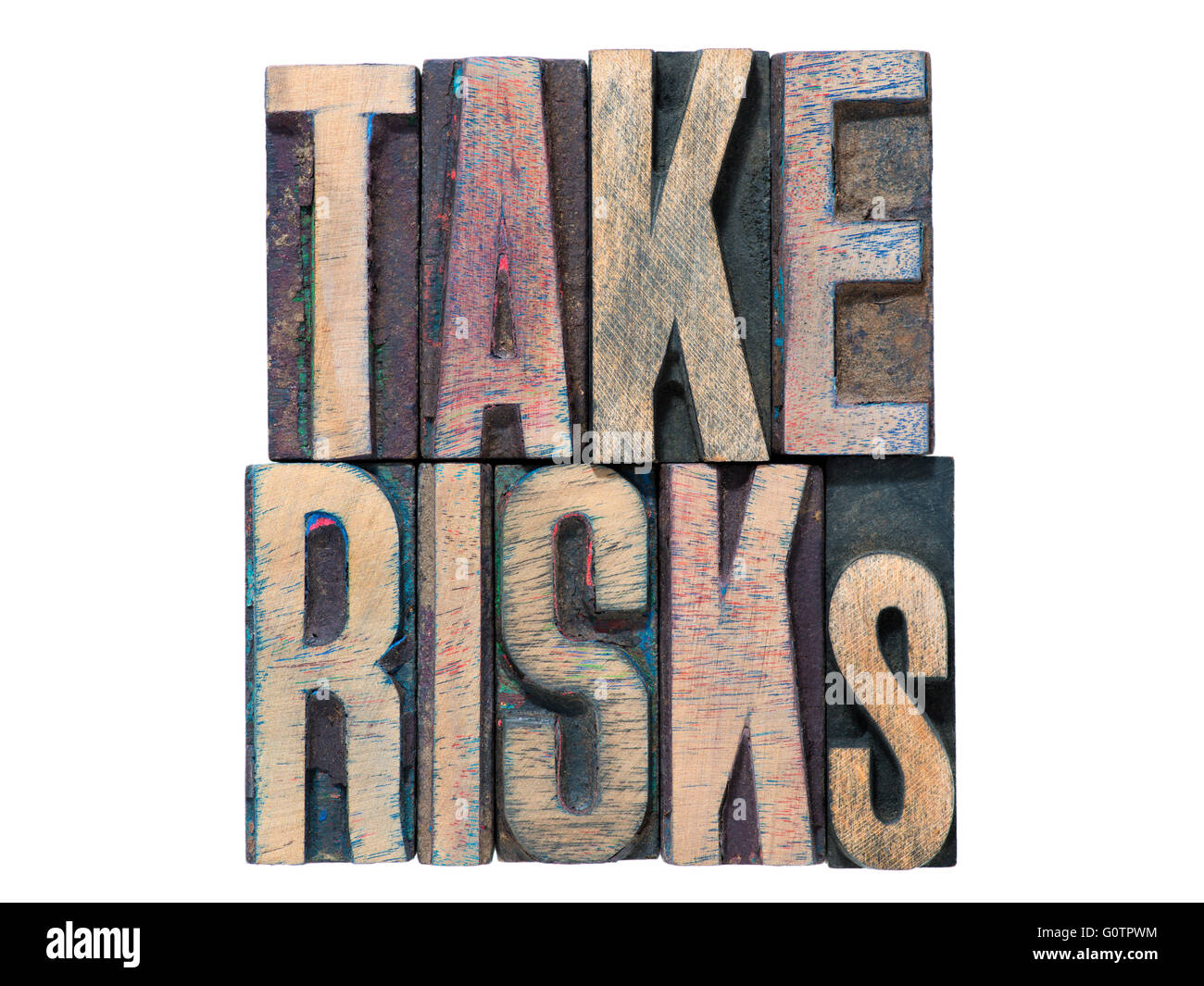 take risks phrase made from mixed wooden letterpress type isolated on white - Stock Image