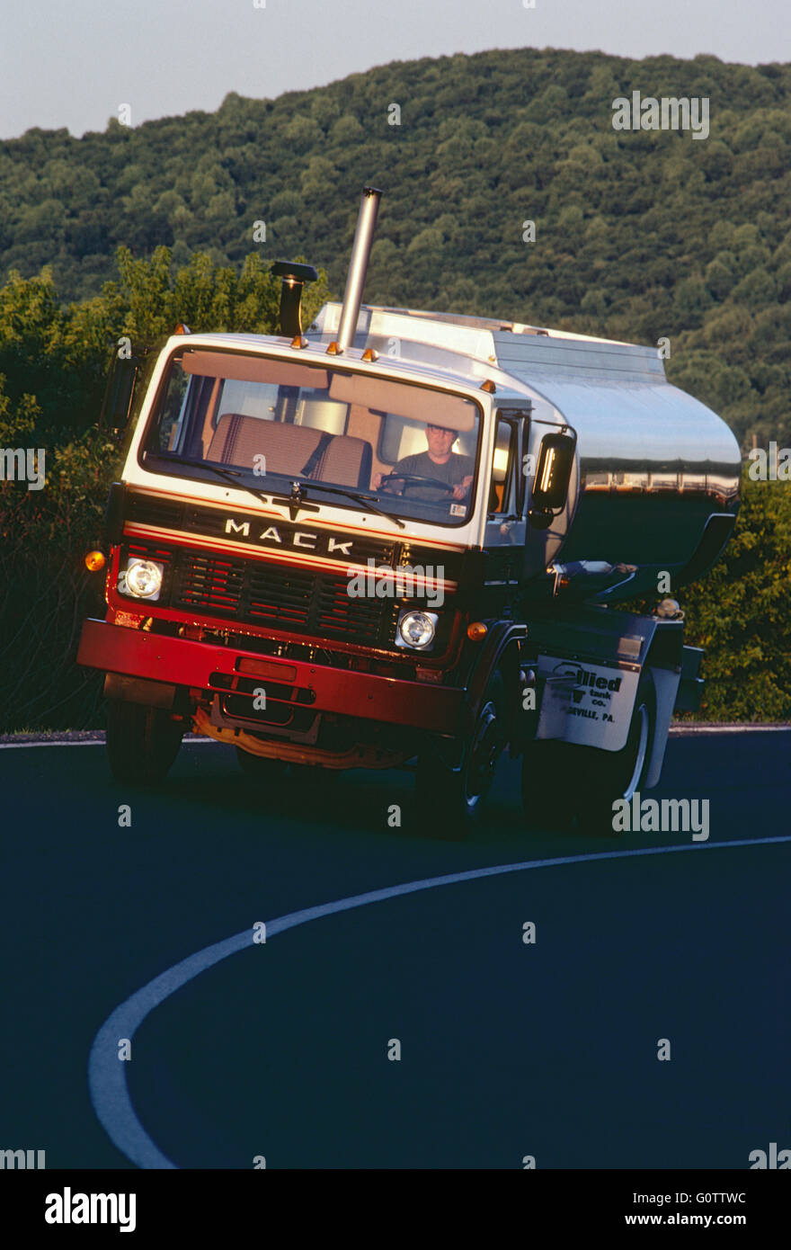 Fuel oil tanker truck traveling at dusk on rural road - Stock Image