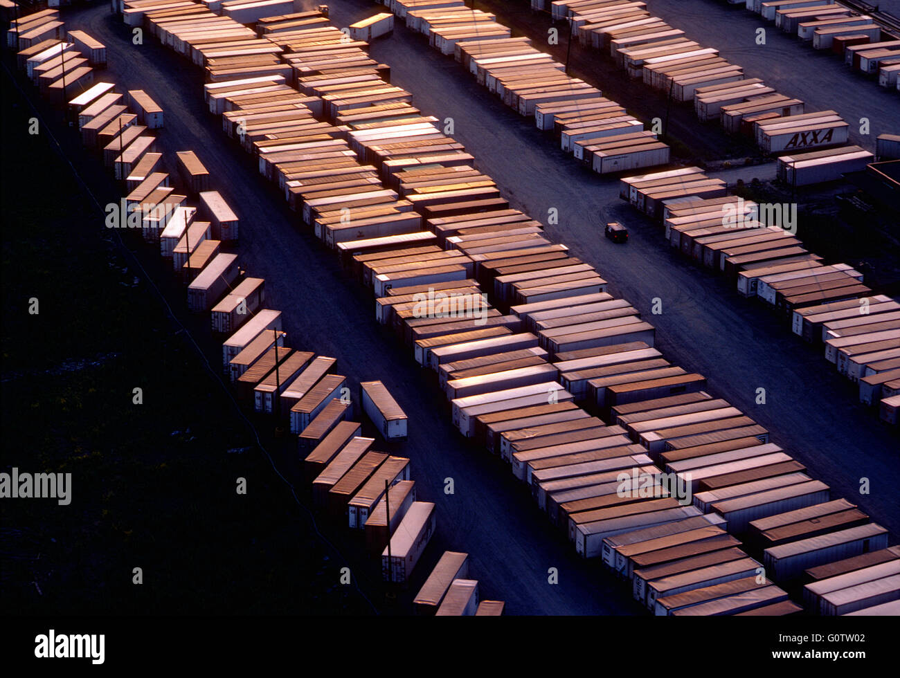 Aerial sunset view of rows of tractor trailers lined up in shipping depot - Stock Image