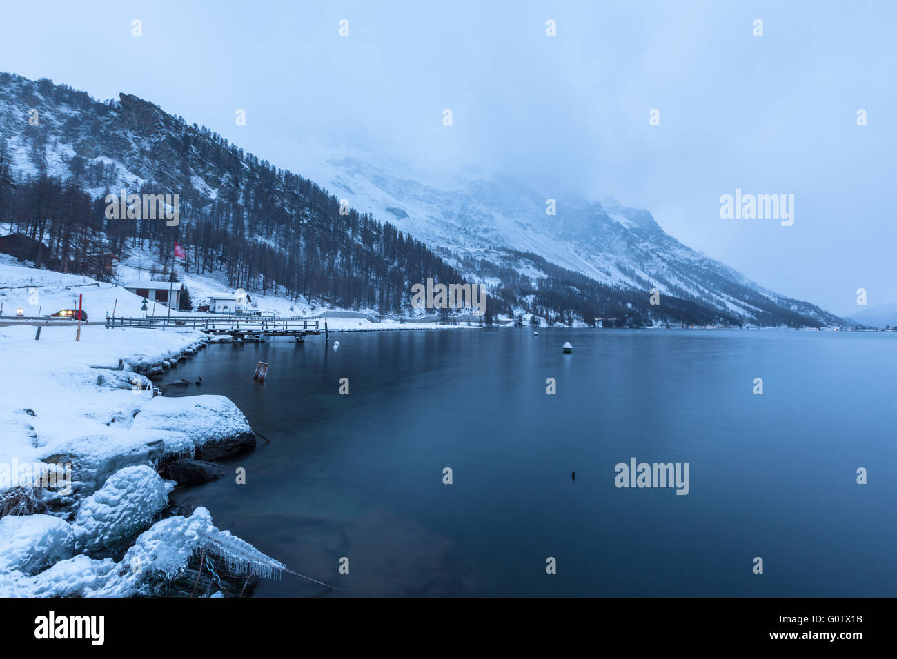View of Sils lake in winter at night fall, small village Plau da Lej, Engadine, Canton of Grisons, Switzerland - Stock Image