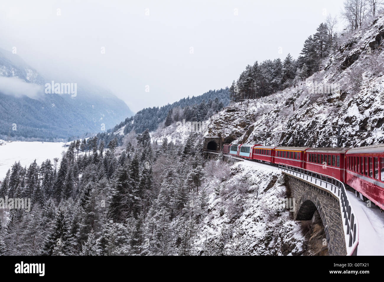 Famous sightseeing train in Switzerland, the Glacier Express in winter - Stock Image