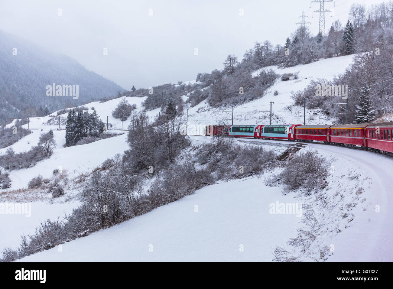 Famous sightseeing train Glacier Express  running in the swiss alps in winter  Switzerland. - Stock Image