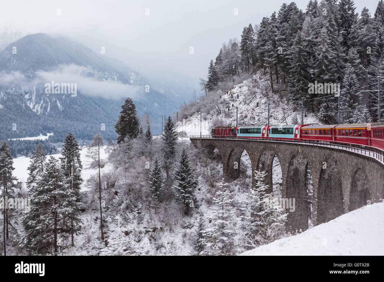 Famous sightseeing train running over viaduct in Switzerland, the Glacier Express in winter - Stock Image