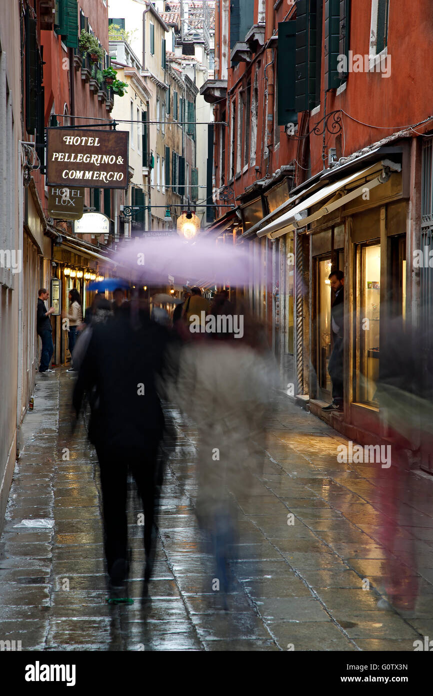 People with umbrellas on wet street, Venice, Italy - Stock Image