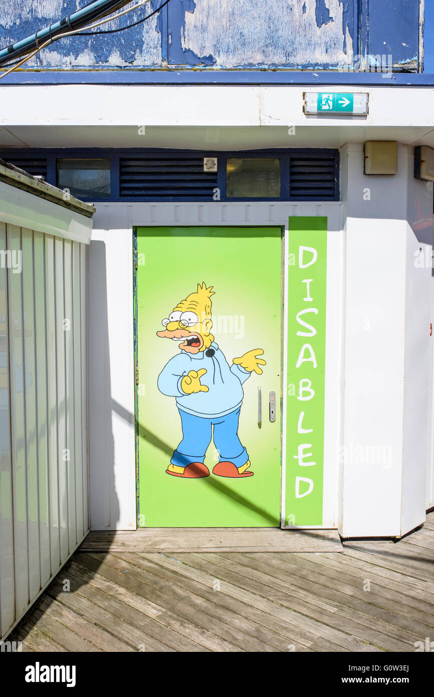 Cartoon character Grandpa Simpson depicted on the door of a disabled public toilet on Central Pier in Blackpool, - Stock Image