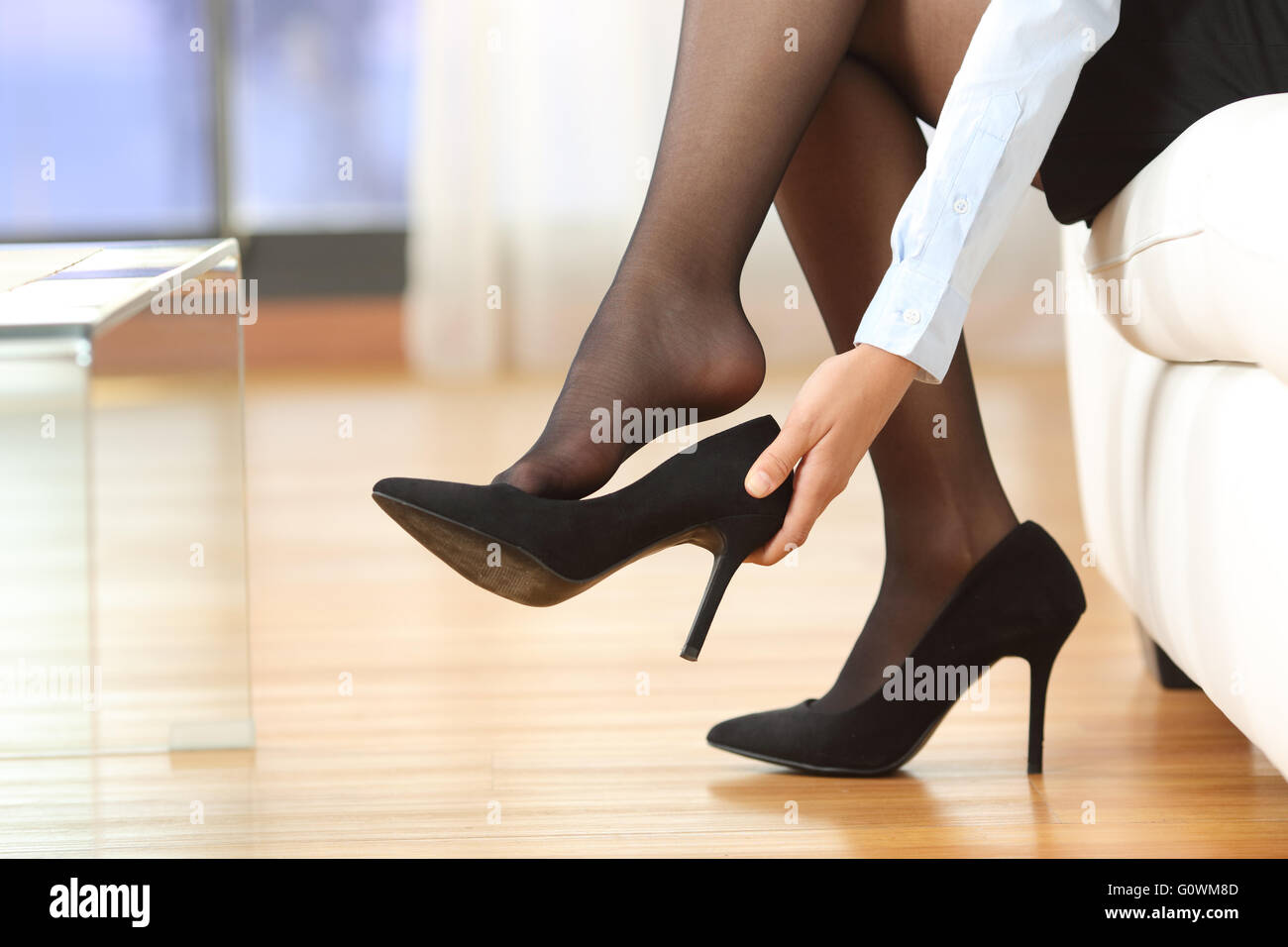 Businesswoman taking off high heels shoes after work at home - Stock Image