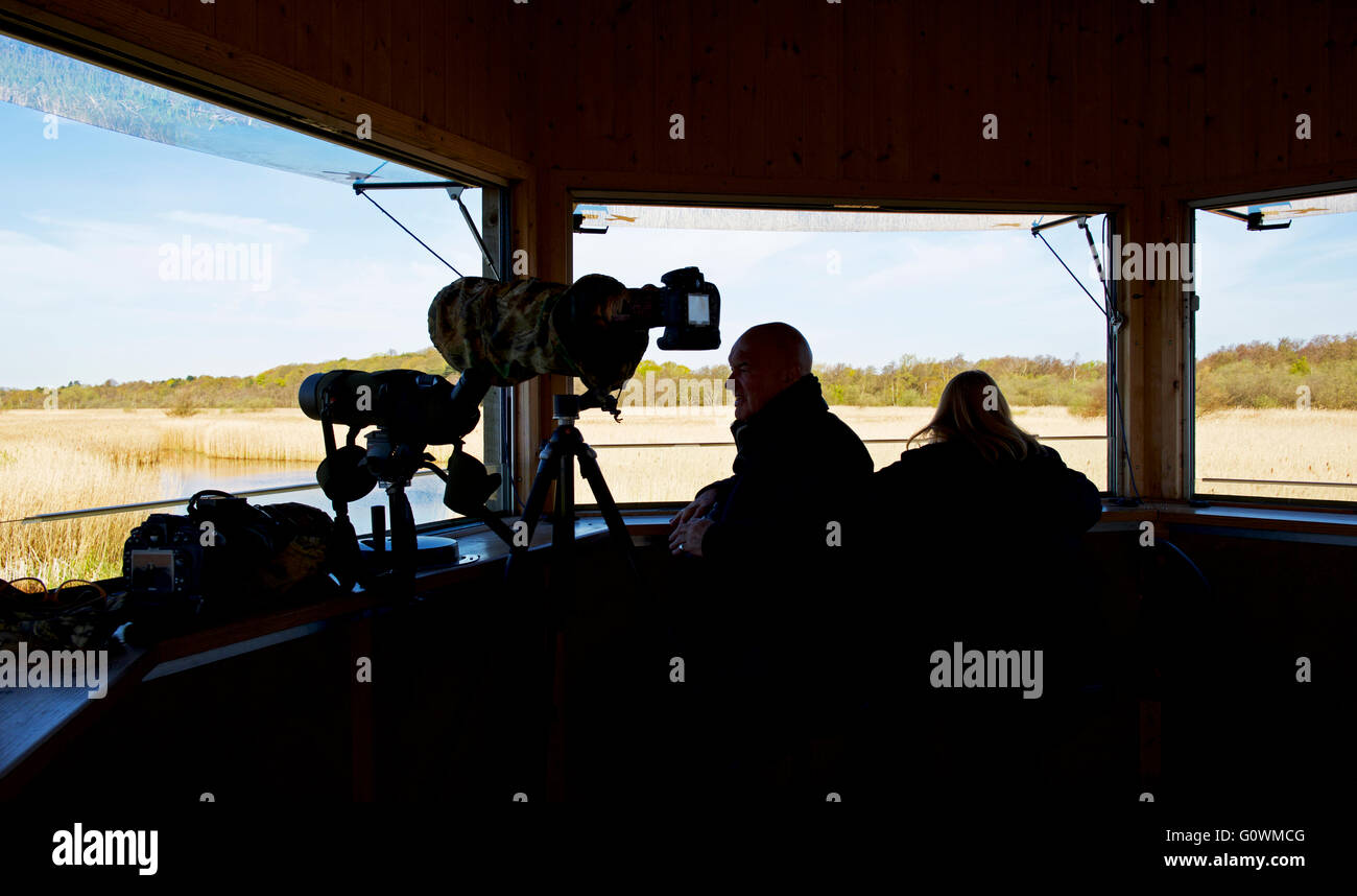 Bird watchers in observation hide at Minsmere, an RSPB bird reserve, Suffolk, England UK - Stock Image