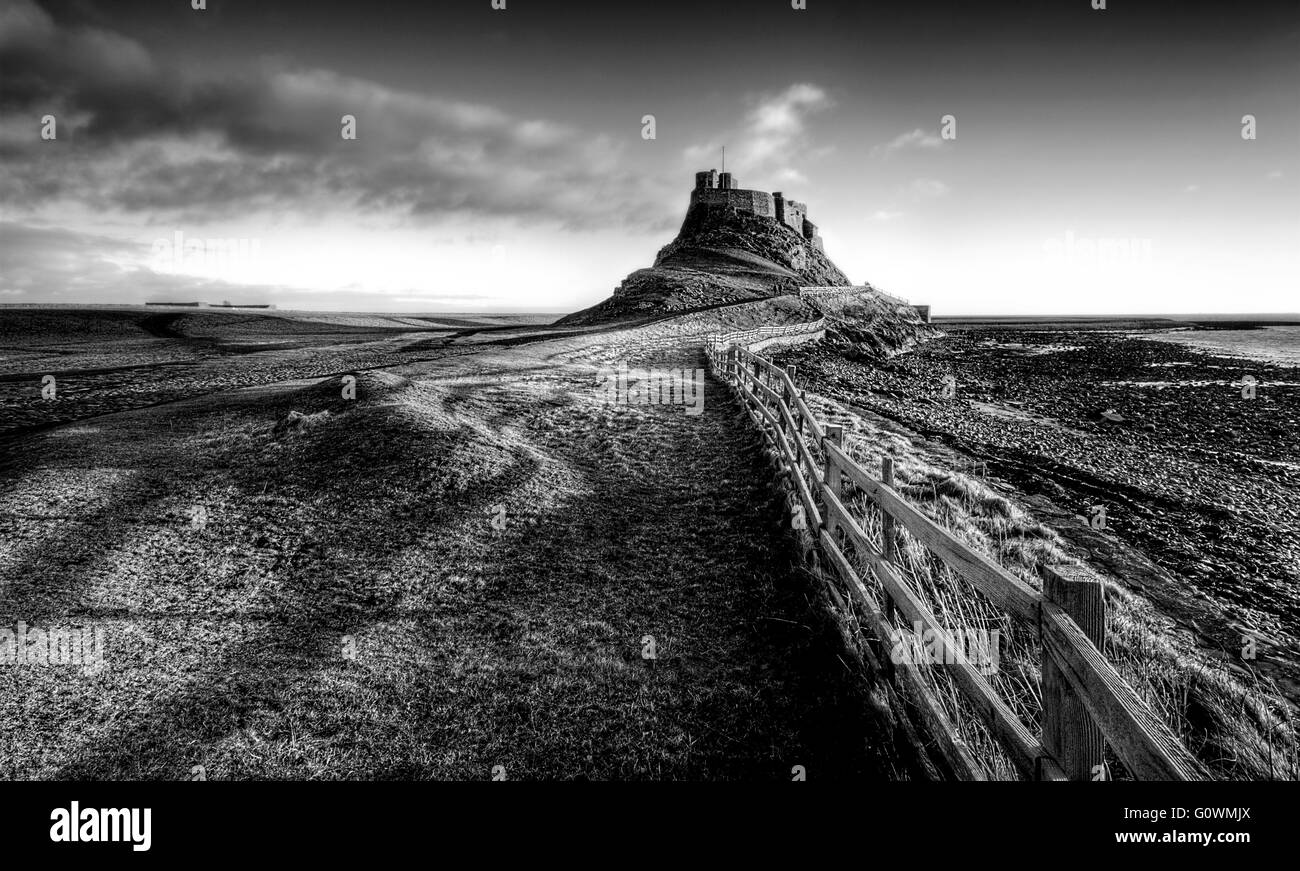 Crooked fenceline leading up to the beautiful Lindisfarne Castle, with the sidelight casting shadows of the fence - Stock Image