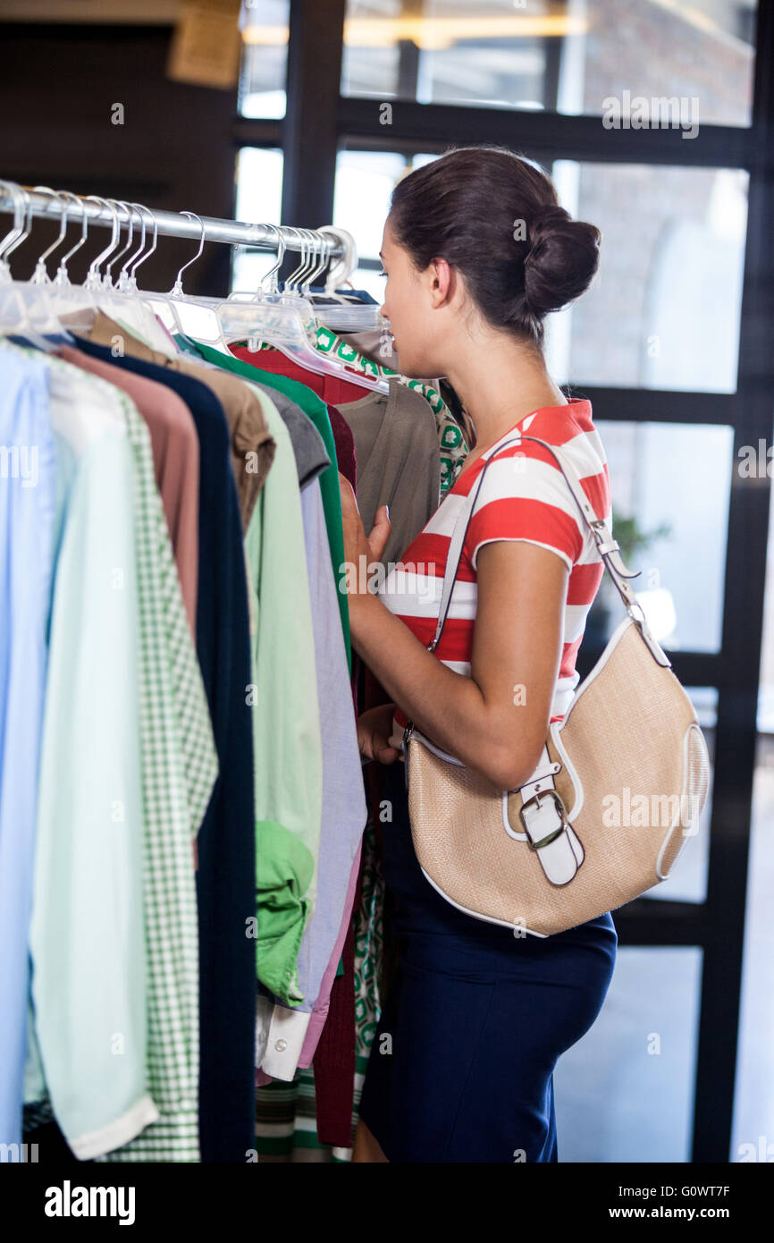 Side view of woman choosing clothe - Stock Image