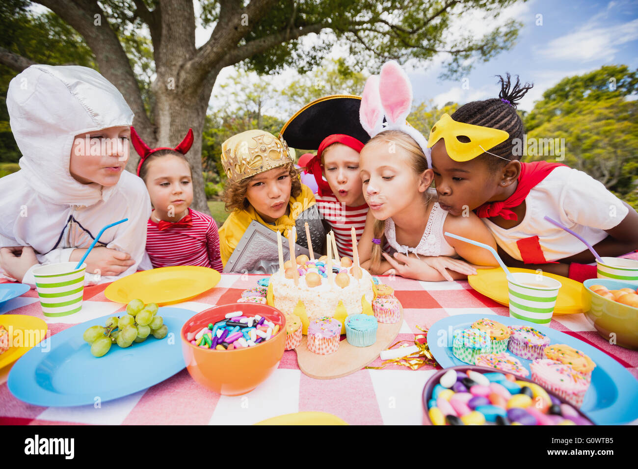 Cute children blowing together on the candle during a birthday party - Stock Image