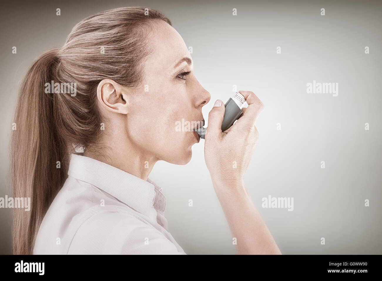 Composite image of pretty blonde using an asthma inhaler - Stock Image