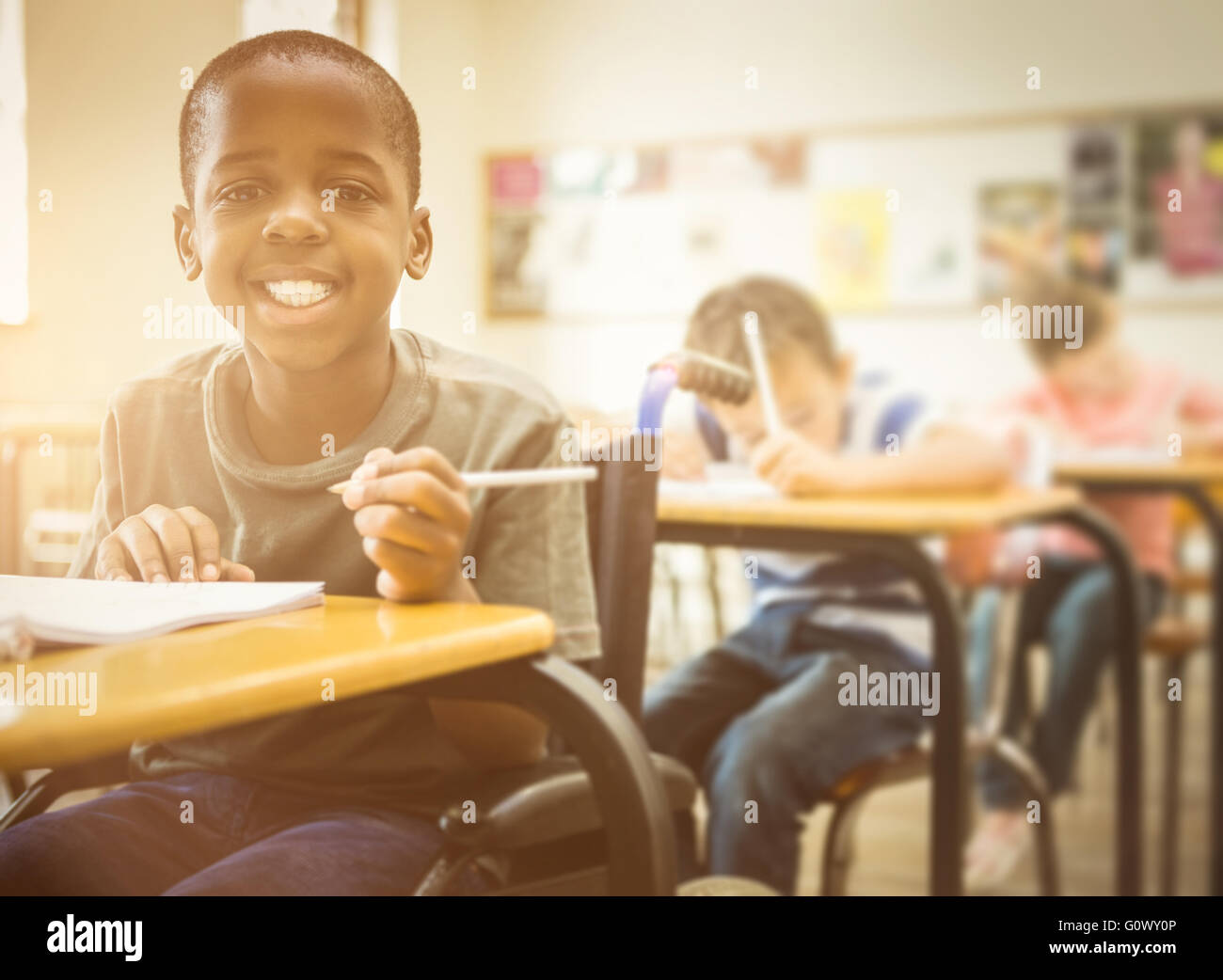 Disabled pupil smiling at camera in classroom - Stock Image