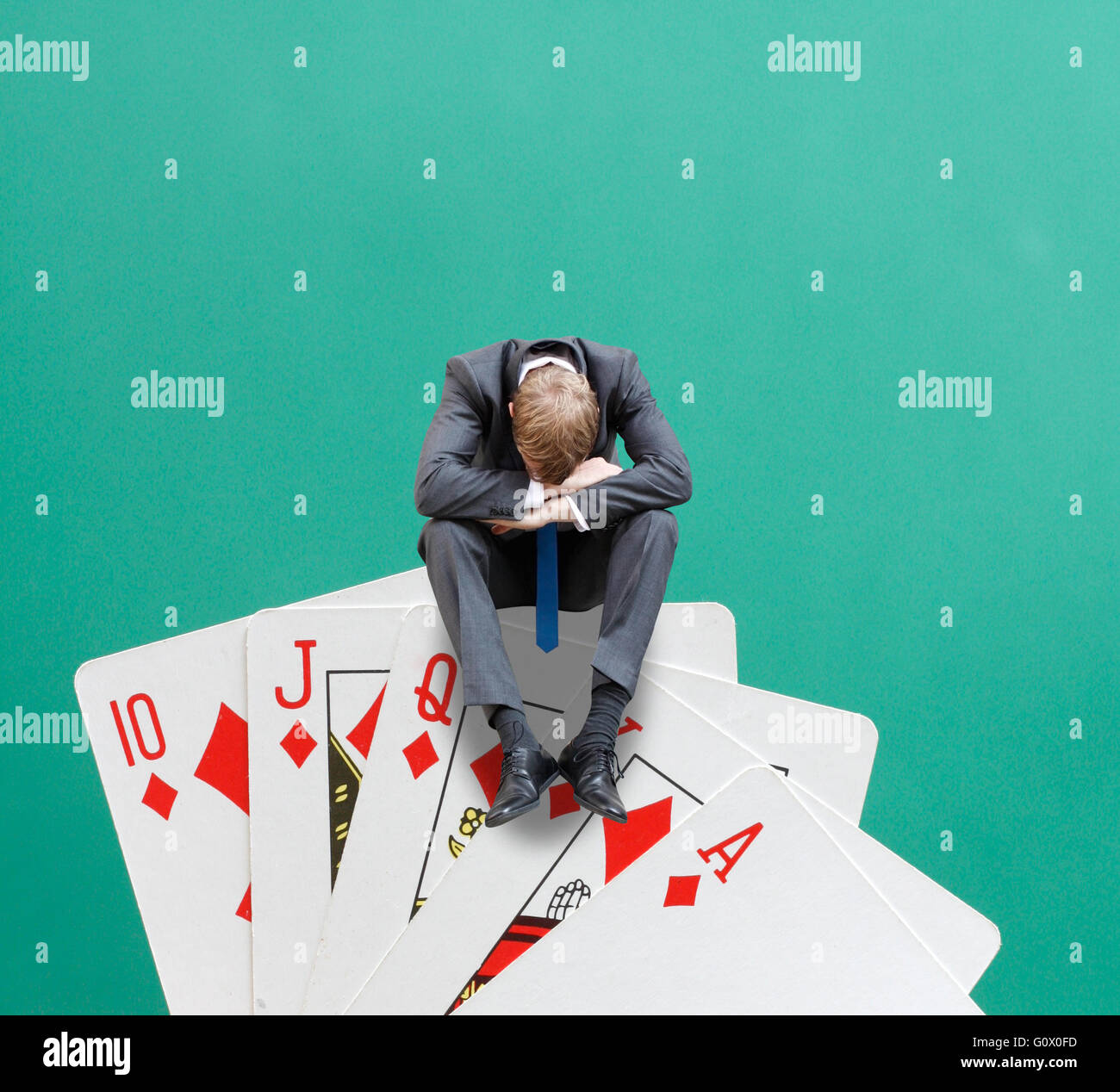 A gambler sitting on cards - Stock Image